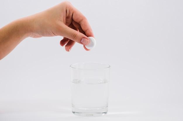 La mano della donna che tiene pillola bianca sopra il bicchiere d'acqua contro il contesto grigio