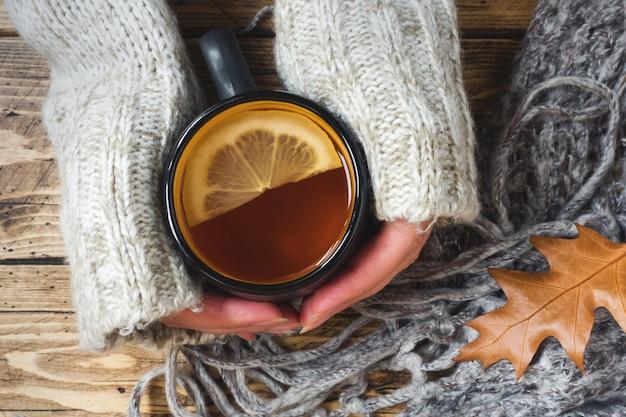 La mano della donna che tiene tazza di tè al limone in una giornata fredda.