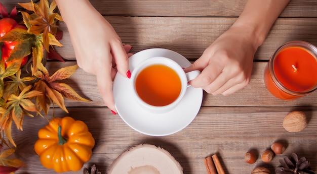La mano della donna che tiene tazza di tè.