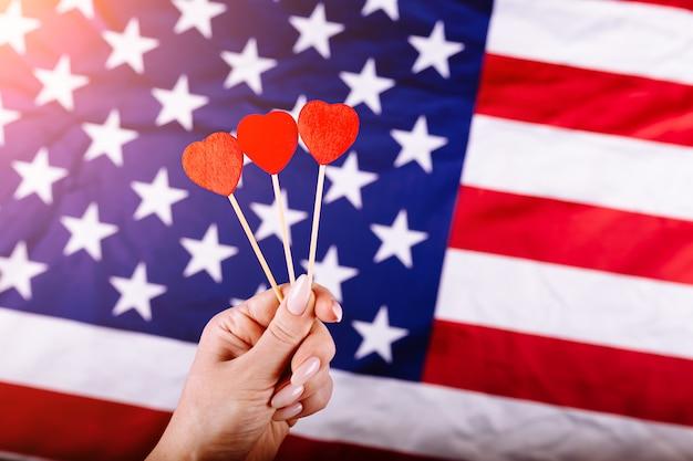 La mano della donna che tiene tre cuori rossi modella sul bastone davanti alla bandiera americana