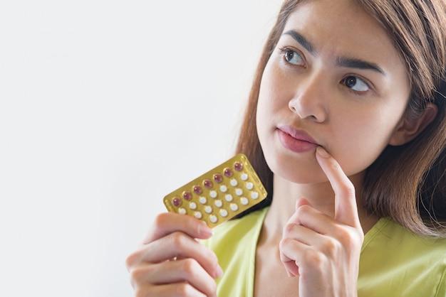 La mano della donna che tiene un pannello contraccettivo impedisce la gravidanza