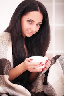 La mano della donna che tiene una tazza di caffè. con una bella manicure invernale. bevi, moda, mattina