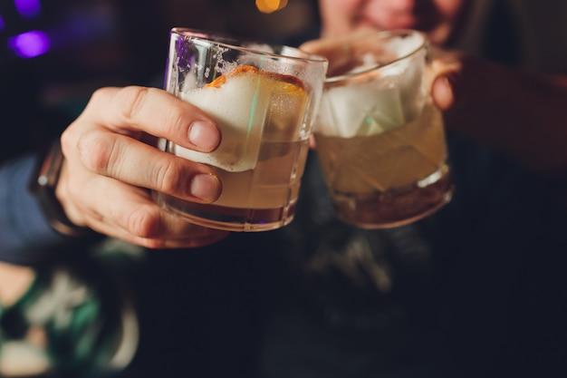 La mano della donna che tiene vetro antiquato con il cocktail freddo contro il fondo vago del night-club.