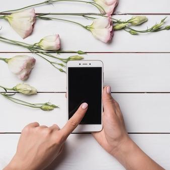 La mano della donna che tocca lo schermo di visualizzazione mobile e i fiori di eustoma sopra lo scrittorio di legno