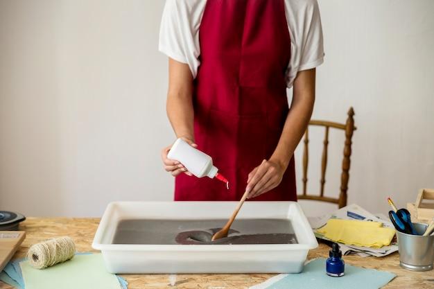 La mano della donna che versa la colla in polpa di carta sullo scrittorio di legno