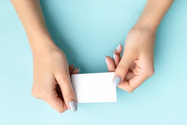 La mano della donna con il biglietto da visita alla moda della tenuta del manicure