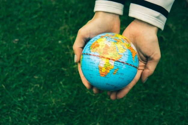 La mano della donna con il globo su fondo verde.