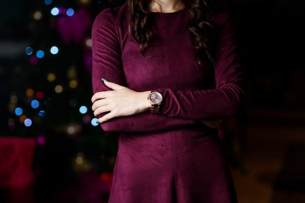 La mano della donna con il guanto rosso che tiene un orologio da tasca