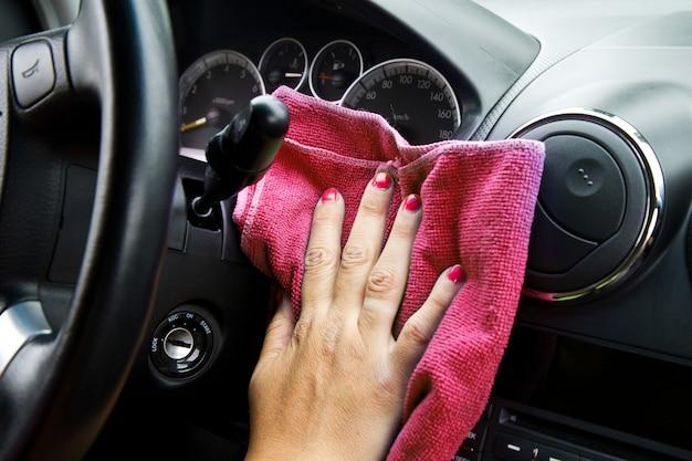 La mano della donna con il panno in microfibra lucidatura ruota di un'auto