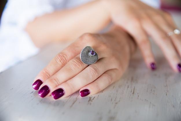La mano della donna con l'anello che tiene tazza di cappuccino