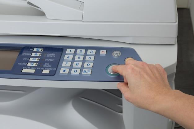La mano della donna con la copiatrice funzionante isolata