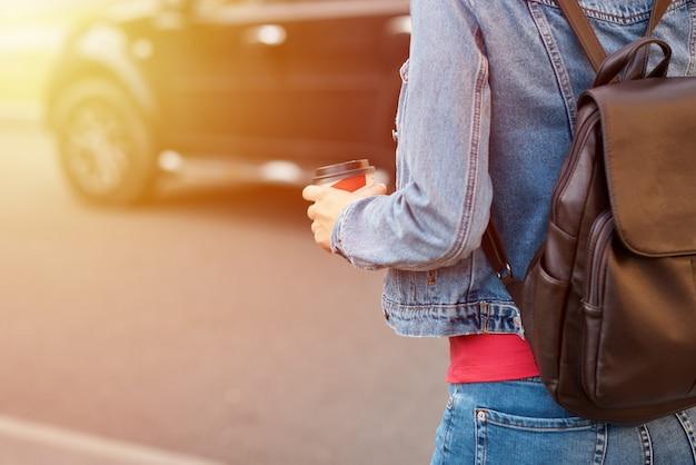 La mano della donna con la tazza di caffè di carta porta via in una via della città