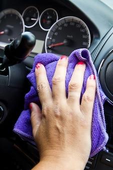 La mano della donna con un panno in microfibra che lucida una macchina