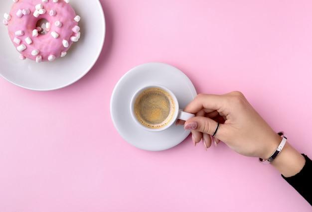 La mano della donna curata che tiene tazza di caffè bianca