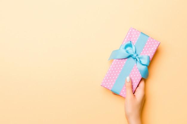 La mano della donna dà il contenitore di regalo del biglietto di s. valentino, vista superiore