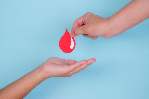 La mano della donna dà una goccia di sangue rosso ad una mano del ragazzo per il concetto di donazione di sangue, giornata mondiale del donatore di sangue.
