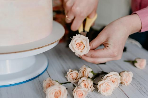 La mano della donna decora la torta di compleanno di nozze rosa con fiori freschi.