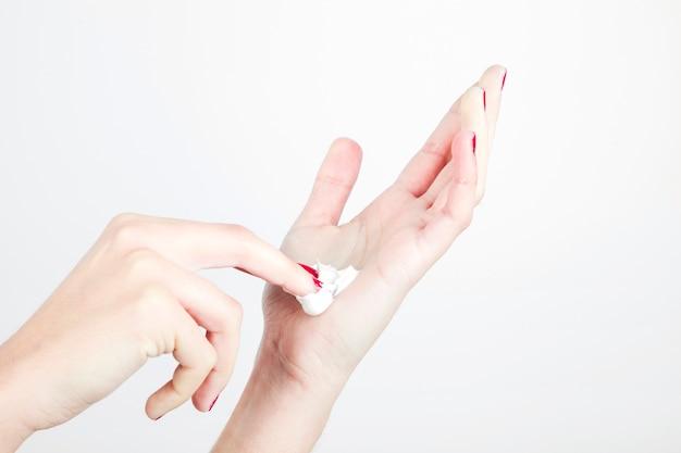 La mano della donna del primo piano con idratante isolato su fondo bianco
