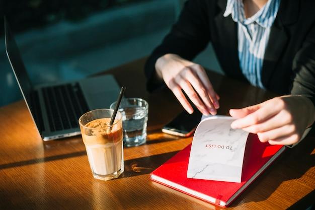 La mano della donna di affari che controlla per fare lista in ristorante