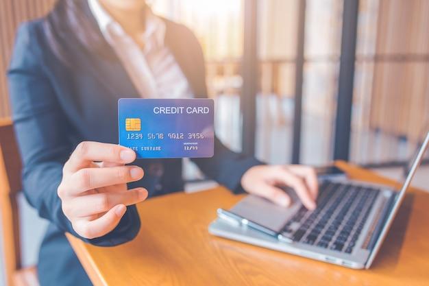 La mano della donna di affari tiene una carta di credito blu. e sta usando un computer portatile