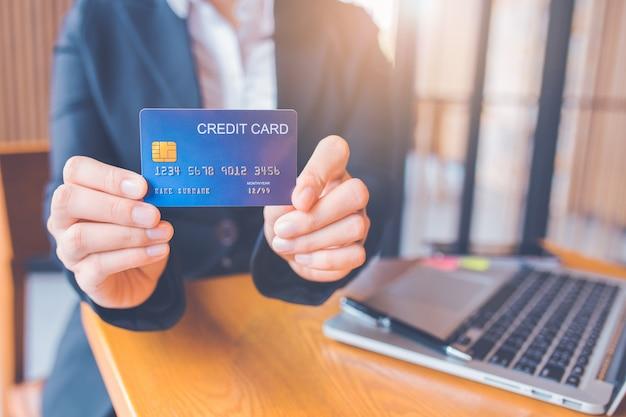 La mano della donna di affari tiene una carta di credito blu.