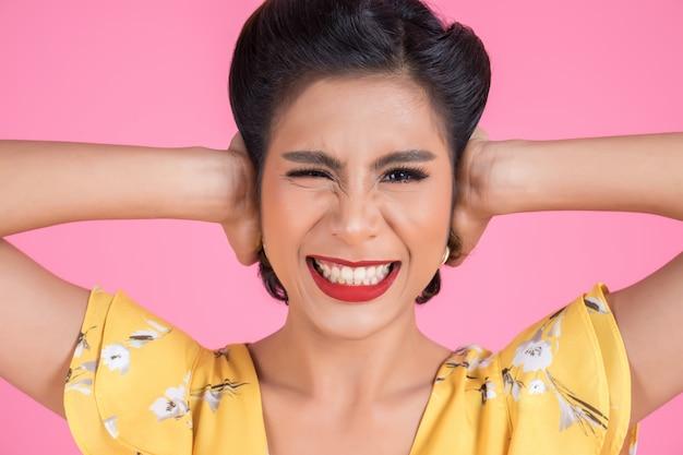 La mano della donna di modo copre le sue orecchie