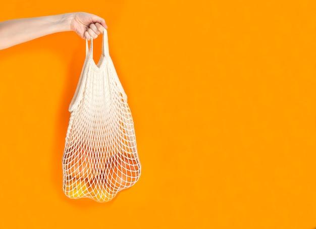 La mano della donna è sulla borsa di stringa con le arance e i pompelmi su fondo arancio.