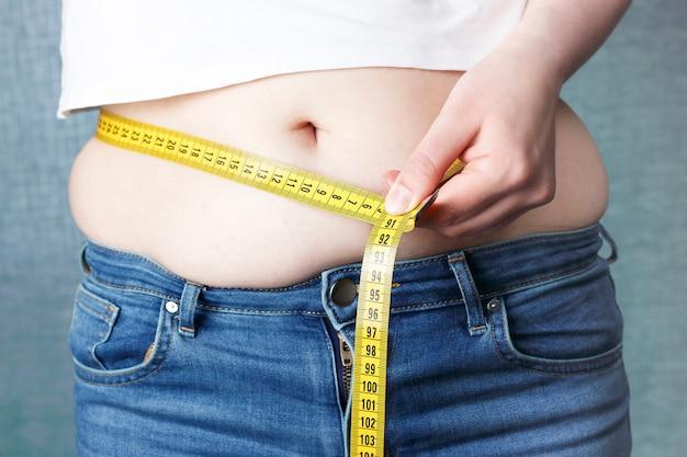La mano della donna misura il suo stomaco con un metro a nastro