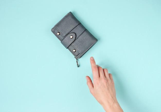 La mano della donna prende un portafoglio di cuoio sull'azzurro. vista dall'alto