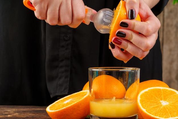 La mano della donna schiaccia la fine del succo di arancia in su