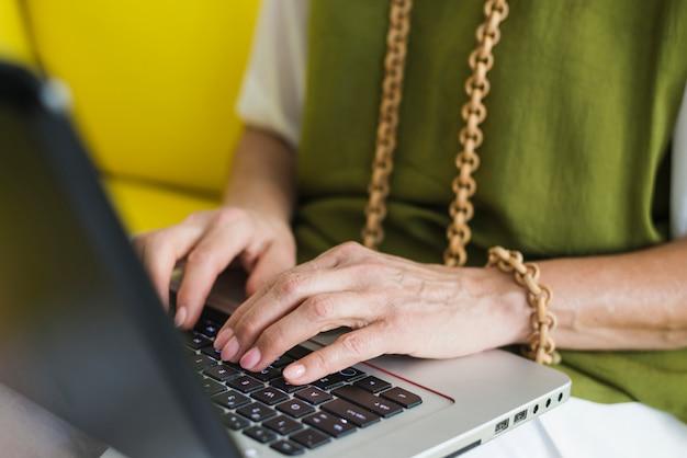 La mano della donna senior sulla tastiera del computer portatile