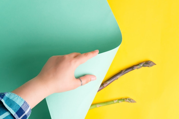 La mano della donna sta girando il foglio di carta colorato turchese pastello su uno sfondo giallo con nuovi germogli di asparagi naturali.