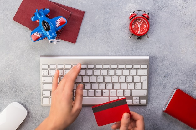 La mano della donna sta scrivendo la tastiera e prende la carta di credito vicino al piccoli orologio e passaporti dell'aeroplano