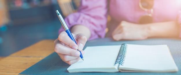 La mano della donna sta scrivendo su un blocco note con una penna. bandiera di web.