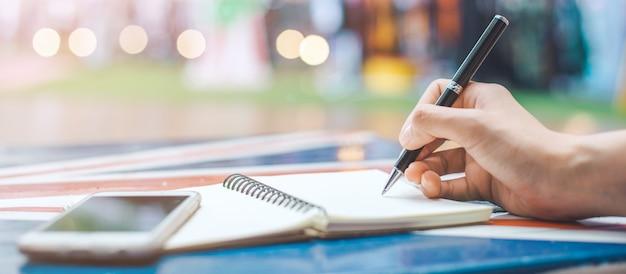 La mano della donna sta scrivendo su un blocco note in bianco con una penna su uno scrittorio di legno bandiera di web.
