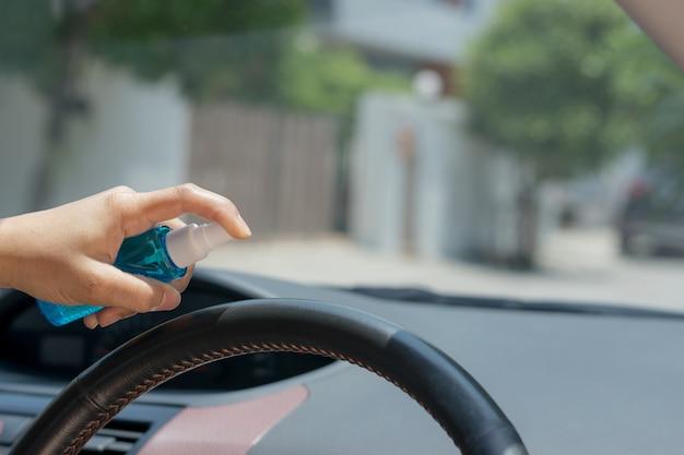 La mano della donna sta spruzzando alcool, spray disinfettante sul volante della sua auto, scoppio di covid-19