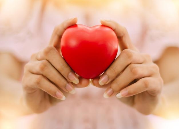 La mano della donna tiene in mano un cuore di gomma rossa per mostrare amore a san valentino.