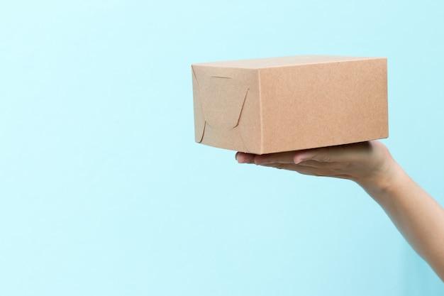 La mano della donna tiene la scatola ondulata marrone sulla parete blu