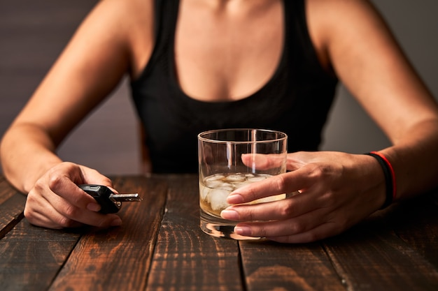 La mano della donna ubriaca che tiene un bicchiere di alcol e una chiave della macchina. concetto di alcolismo e incidenti stradali causati dall'alcol.