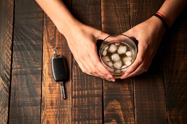 La mano della donna ubriaca che tiene un bicchiere di alcol e una chiave della macchina. concetto di alcolismo e incidenti stradali.