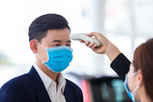 La mano della donna usa un termometro digitale a infrarossi medico, usa un monitor della temperatura corporea di un giovane uomo, il concetto di uno screening del virus corona [covid-19].