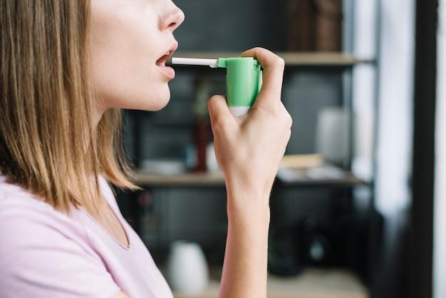 La mano della donna usando spray per la gola