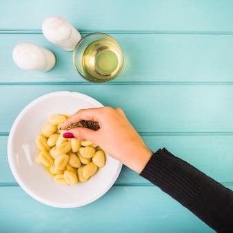 La mano della femmina aggiungendo condimento sulla pasta di gnocchi