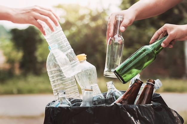 La mano della gente che tiene la bottiglia di immondizia plastica e vetro che mette nel ricicla la borsa per pulire