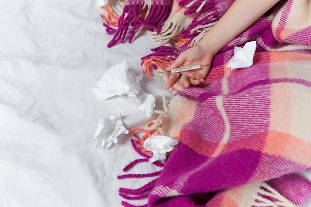 La mano della giovane donna malata con termometro