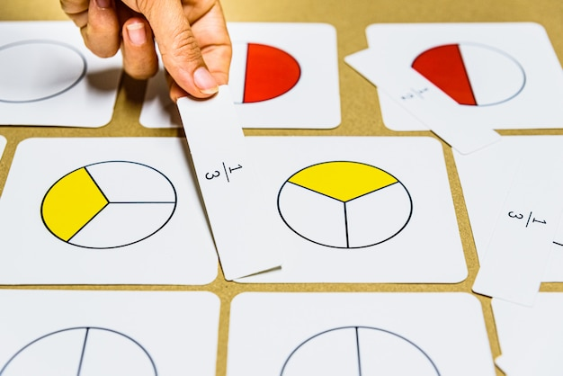 La mano della guida montessori dell'insegnante mostra graficamente le frazioni con le carte matematiche.