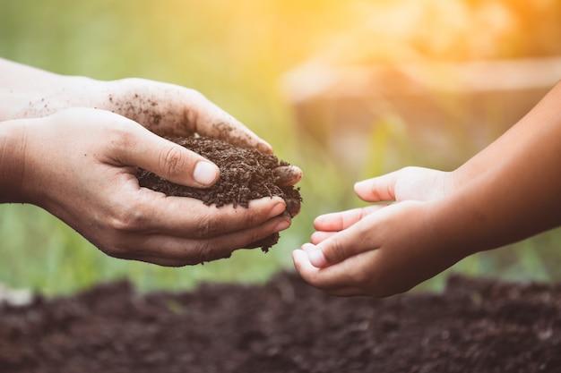 La mano della madre che dà il terreno ad un bambino per piantare insieme nel tono di colore vintage