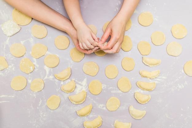 La mano della mamma e del bambino produce i ravioli