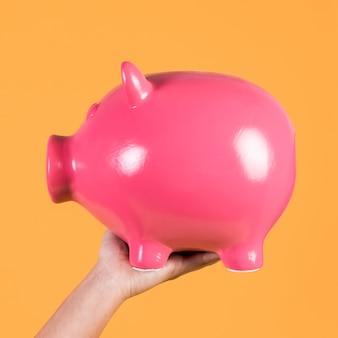La mano della persona che mostra concetto di risparmio con il porcellino salvadanaio
