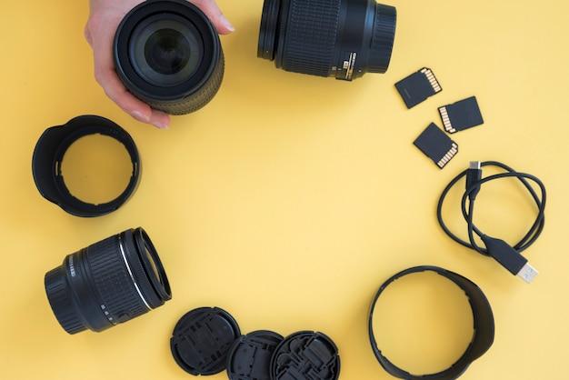 La mano della persona che organizza gli accessori della fotocamera in forma circolare su sfondo giallo